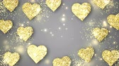 Gold shining hearts sparkle on the gray background with place for text. Valentines Day holiday abstract loop animation.