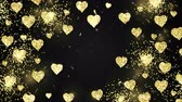 написанный : Gold shining hearts sparkle on the black background with glow animated text. Valentines Day holiday abstract loop animation. Стоковые видеозаписи