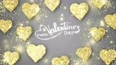 Gold shining hearts sparkle on the gray background with glow animated text. Valentines Day holiday abstract loop animation. Stock Footage