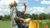 bolsa : Middle-aged woman drinking water from a bottle