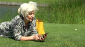 handbag : Middle-aged woman relaxing on grass beside a lake Stock Footage