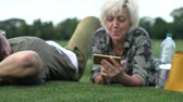 film : Mature woman lying on grass in a park