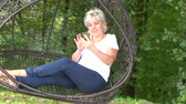 socialising : Blond woman sitting in a mesh swing seat