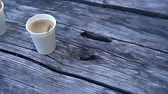 gobelet carton : Two cups of takeaway coffee on an old wooden table Vidéos Libres De Droits