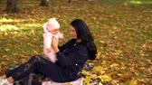 nevetés : Young woman in black playing with baby in park