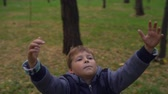 достигать : Boy with hands up standing in park and spinning
