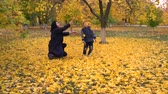 ahornbaum : Young woman and boy playing with yellow leaves Stock Footage