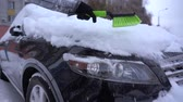 visibilité : Cleaning snow off the black car headlight
