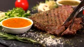 specialita : Person cutting rump steak and dipping in a sauce