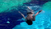 chutando : Young woman swimming in a blue pool