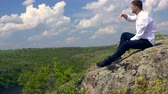поднятый : Young man sitting on a high rocky outcrop