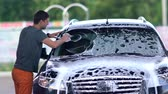 soapy : Young man washing the windscreen on his car Stock Footage