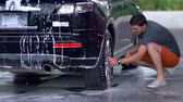 обод : Young man cleaning his black saloon car Стоковые видеозаписи