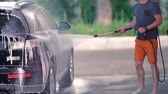 hosepipe : Young man hosing soap suds off his car