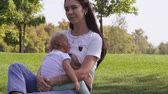 Young mother breast feeding her young daughter Stock Footage