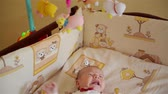 fizet : Little cute baby boy lying in crib with toy Stock mozgókép