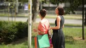 shopaholic : Beautiful smiling female friends with shopping bags in hands walking by street Stock Footage