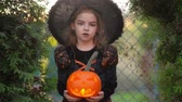 assombro : Halloween. Cute girl shows a cheerful witch. She is dressed in a black dress and hat. Girl holding pumpkin with a burning candle and screaming into the camera.
