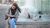 sem fio : Beautiful Girl reading and browsing an ebook or a tablet sitting in a bench at the street, fountain background Vídeos