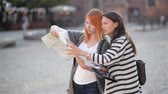??ken : Two young attractive girls are looking aside in the urban zone while exploring the city. Caucasian women are walking with the paper map to find interesting places while travelling.
