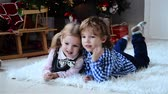 brother : Happy Cute little boy and his beautiful sister at Christmas, children laughing while lying on the floor near a Christmas tree Stock Footage