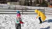 travessura : Happy Mother is Playing in Snowball Fight with Her Daughter Outdoors. Woman in Yellow Coat and Little Girl are Having Fun Together Outside During Winter Vacation in the Mountains.
