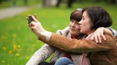 зрелом возрасте : Mature Daughter and Her Mother are Using Smartphone During the Picnic in the Park. Two Smiling Brunette Women are Taking Selfie Outdoors.