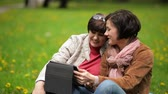 зрелом возрасте : Mother and Daughter are Using Mobile Device Together Outdoors. Young Woman is Showing Somthing to Her Mom on Tablet Screen in the Park.