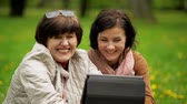 зрелом возрасте : Mature Brunette Woman is Showing Something on the Tablet Screen to Her Laughing Mother. Happy Family Spending Time Together with Electronic Device During Picnic in the Park.