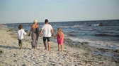 brother : Back View of Four Members of Happy Family Walking on the Beach During Summer Vacation on the Seaside.