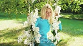 rosas : Attractive blonde on a swing made of flowers