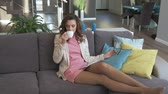 interesting : Charming brunette woman relaxing in a luxurious living room Stock Footage