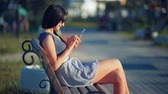 Beautiful woman sitting on the outdoor bench and typing on the phone