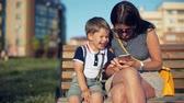 Mother and her small son are laughing and watching something on smart phone in park