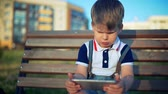 Child playing with smart phone in the park outdoors.
