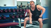 Muscular bodybuilder guy doing exercises with dumbbells in the gym.