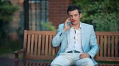 Young businessman talking on the phone in the park Vídeos