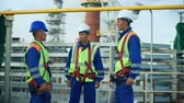 Three workers in production plant as team discussing, industrial scene in background