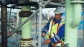 Asian worker rotating wheel at large oil refinery.