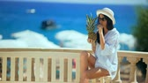 Pretty woman in white hat with tropical cocktail on the beach enjoying sunny weather looking at the ocean view. Stock Footage