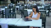 Beautiful young woman with a laptop working in modern cafe.