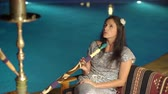 Attractive girl smoking hookah near the pool with blue water background. Stock Footage