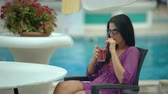 Young stylish beautiful woman drinking tropical cocktail near resort pool Stock Footage
