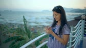 Relaxed woman using a smart phone in a bar or hotel terrace on holidays. Stock Footage