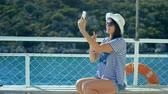 Attractive young woman on yacht taking a selfie photo