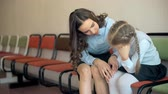 krutý : A female teacher sits consoling a young school sad girl in the corridor Dostupné videozáznamy