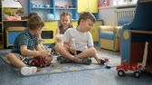 азбука : Four children are playing on the floor with toys
