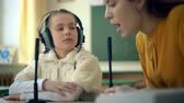 deaf : Young girl and teacher using headphones and microphone in the classroom Stock Footage