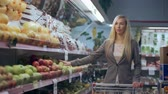 grocer : Beautiful young woman with trolley shopping in supermarket Stock Footage