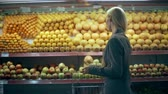 grocer : Young woman choosing oranges in grocery store